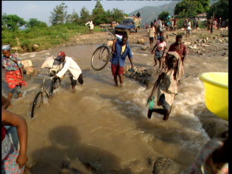 Villagers followed by truck cross flooded river Democratic Republic of Congo