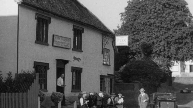1937 MONTAGE Villagers gather outside the pub and gossip / Essex, England