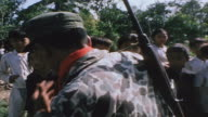 Villagers lining riverbank soldier walking past carrying M16 PBR crew coming ashore with slung M16s and speaking with villagers / Vietnam