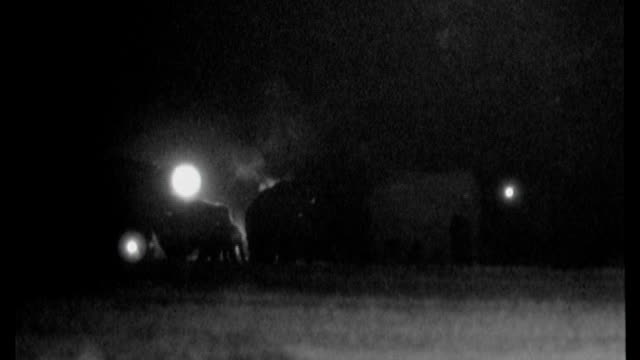 Villagers with flaming torches chase elephants out of field at night Available in HD.