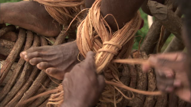Vines being tied to man's ankle during land diving ritual, Pentecost, Vanuatu