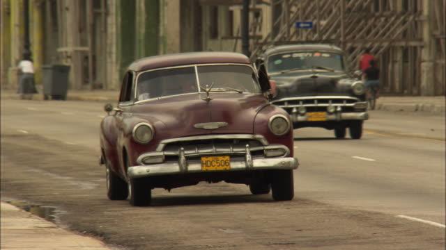 MS, CU, vintage car driving on city street, Havana, Cuba