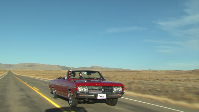 vintage red convertible driving