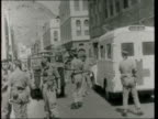 Crater MS Soldier runs to ambulance pan armoured car ZOOM into injured Arab on stretcher BV AGSH troops in street with ambulance and armoured car BV...
