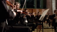 MS Violinists playing in orchestra, conductor leading / London, United Kingdom