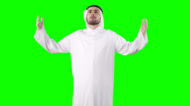 Virtual prayer. Middle eastern ethnicity man rainsing arms on green screen with alpha