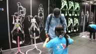 A visitor tries a Muscle suit in the Tokyo University of Science booth at Japan Robot Week 2014 in Tokyo Japan on Wednesday Oct 15 A robot arm...