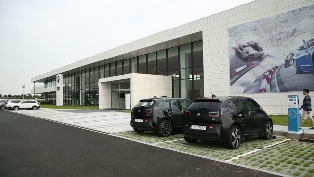 A visitor walks past Bayerische Motoren Werke AG i3 electric vehicles sitting at electrical charging stations at the companys driving center in...