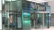 Visitors depart and arrive at the British Telecom BT headquarter offices in central London a advertisement for BT Sport television service hangs...