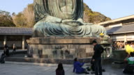 Visitors in front of  the huge Buddha statue at Kotoku-in in the city of Kamakura in Kanagawa Prefecture, Japan