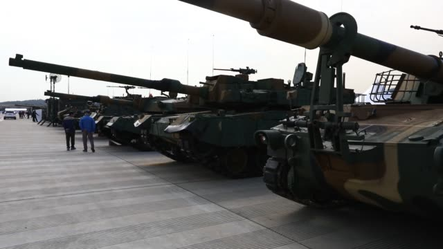 Visitors look at South Korean army tanks on display during a press day of the Seoul International Aerospace Defense Exhibition at Seoul Airport in...