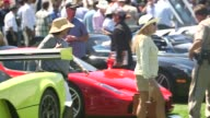 Visitors look at vehicles on display at the Pebble Beach Concours dElegance Car Show in Pebble Beach California US on August 15 2014 Shots of Close...
