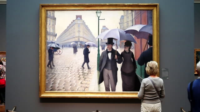 Visitors look over Paris Street Rainy Day by the French artist Gustave Caillebotte at the Art Institute of Chicago on September 17 2014 in Chicago...