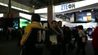 Visitors pass the ZTE Corp pavilion at the Mobile World Congress in Barcelona Visitors test demonstration ZTE smartphones at the ZTE Corp pavilion...
