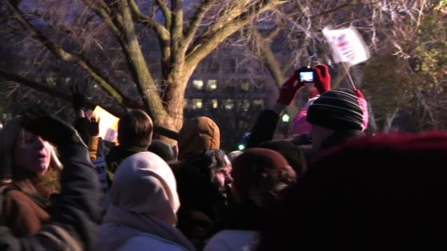 Visitors to the National Mall on the eve of Barack Obama's inauguration at America's first black president watch as MSNBC broadcasts live from during...