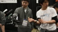 Visitors to the South by Southwest Interactive Festival observe a kiosk featuring a set of robotic hands as they are controlled by a technician in...