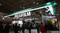Visitors walk past the Fujifilm Holdings Corp booth in exhibition hall Fujifilm at the CP Camera and Photo Imaging Show on January 31 2013 in...