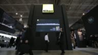 Visitors walk through the Nikon Corp booth inside exhibition hall Nikon at the CP Camera and Photo Imaging Show Pa on January 31 2013 in Yokohama...