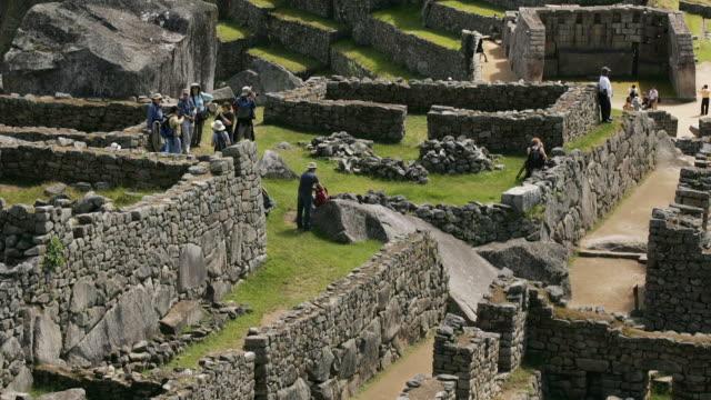 Visitors walk through the Upper Complex at Peru's Machu Picchu ruins.