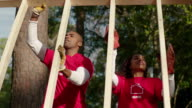 Volunteers lift frame together
