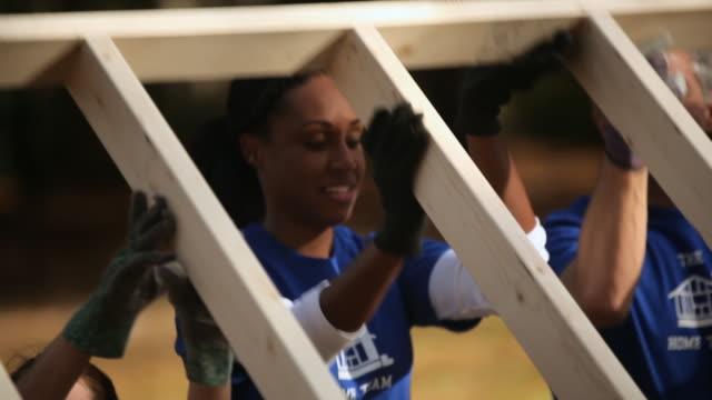 Volunteers lift frame together