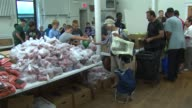 WGN Volunteers pass food to people at Common Pantry in the Epiphany United Church of Christ on the corner of Damen Ave and Bradley Pl in Chicago on...