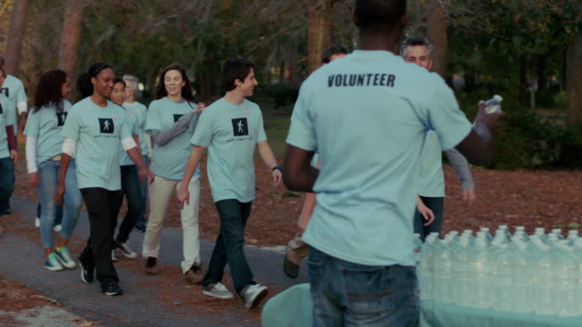 Volunteers pass water station on charity walk