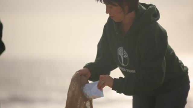 Volunteers picking up trash on beach