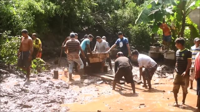 Volunteers remove rubble and debris where four people among them two children died buried by a landslide caused by heavy rains in the community of El...