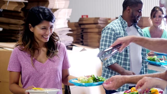 Volunteers serve people in soup kitchen