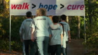 Volunteers walk away under charity banner