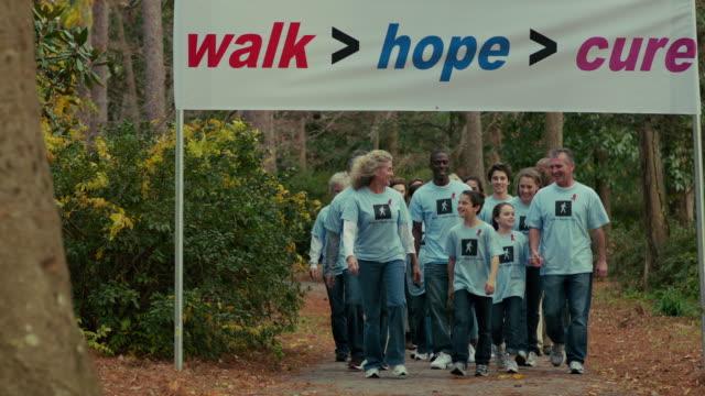 Volunteers walk toward camera under charity banner
