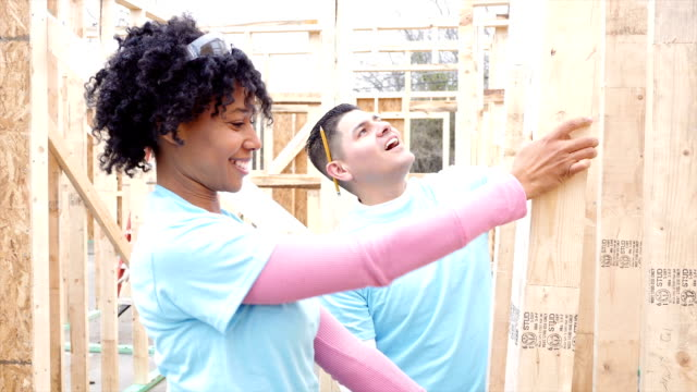 Volunteers work on construction frame on home being built for charity