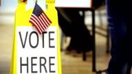 """""""Vota qui"""" accesso.  Persone a piedi, fuori dalla stazione di polling."""