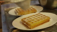 Waffles with icing sugar being sprinkled on tip in Antwerp, Belgium