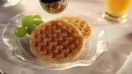 Waffles with syrup being poured over