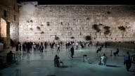 Wailing Wall at night with people in attendance