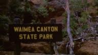 Waimea Canyon Signage Shots of Canyon Beach Resort Sunbathing Mountainside Waimea Canyon State Park on August 01 1975 in Kauai Hawaii