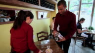Waiter and waitress clearing table in restaurant