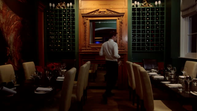 MS Waiter arranging dining table in restaurant