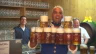 waiter carries beer mugs