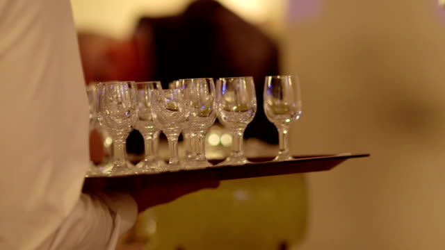 CLOSE UP Waiter holding tray with empty clean wineglasses