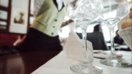 Waiter pouring water into glass in a restaurant.