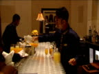 Waiter pours juice into glasses at function in luxury hotel others work busily around him Dubai