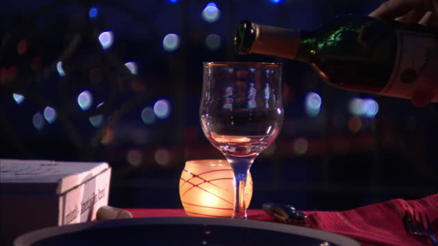 A waiter pours red wine into a wine glass.