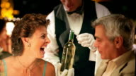 MS waiter pours wine for middle age couple in upscale restaurant / they toast + kiss