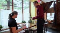 Waiter serving customer in restaurant