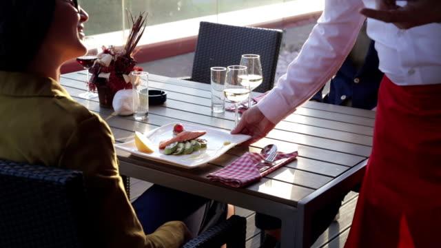 Waiter serving food in outdoor restaurant