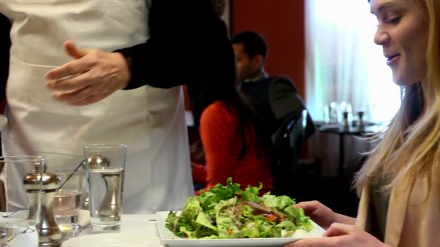 Waiter Serving Salad Meal to Couple