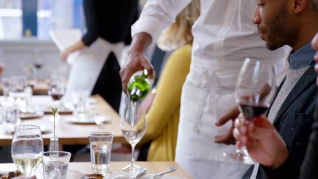MS PAN R/F TD waiter standing at table in restaurant pouring wine for couples dining together